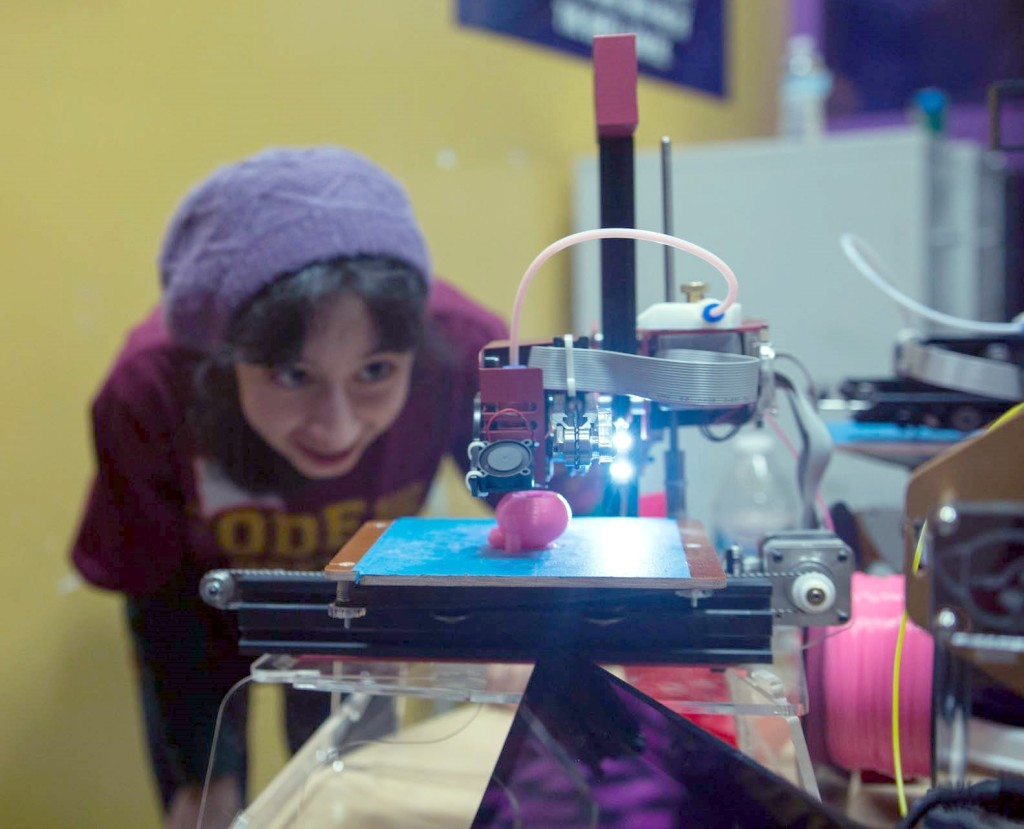 A student watches her 3D printed art come to life.